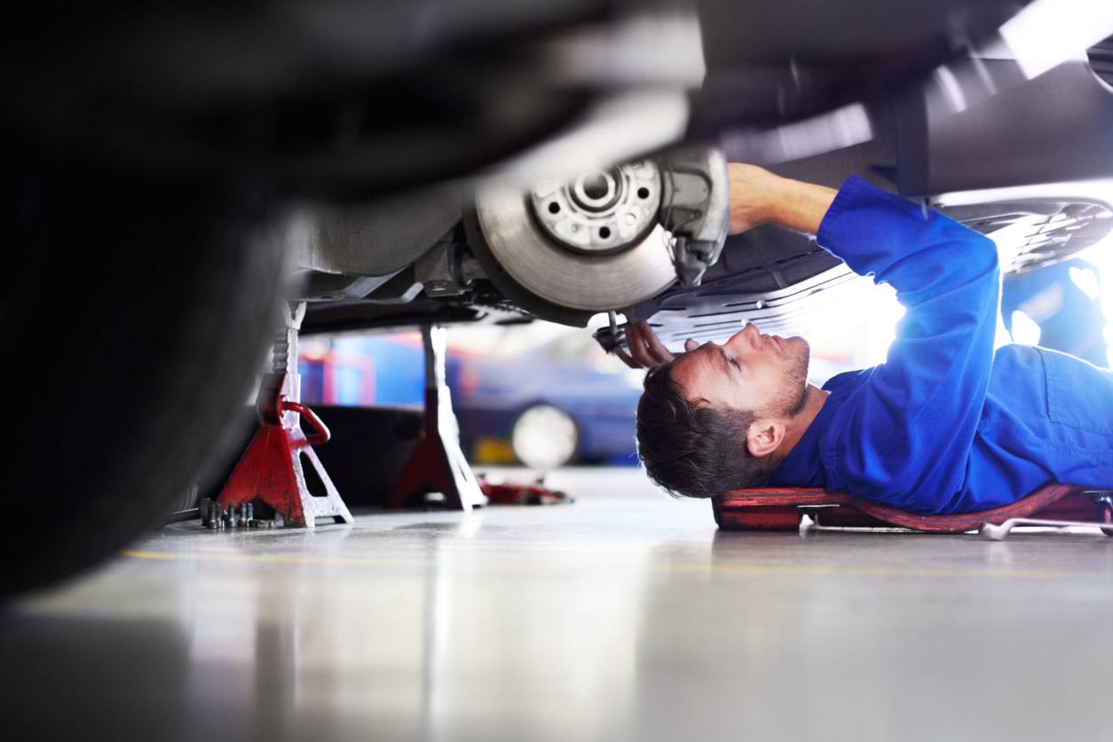 A car mechanic working on the underside of a car